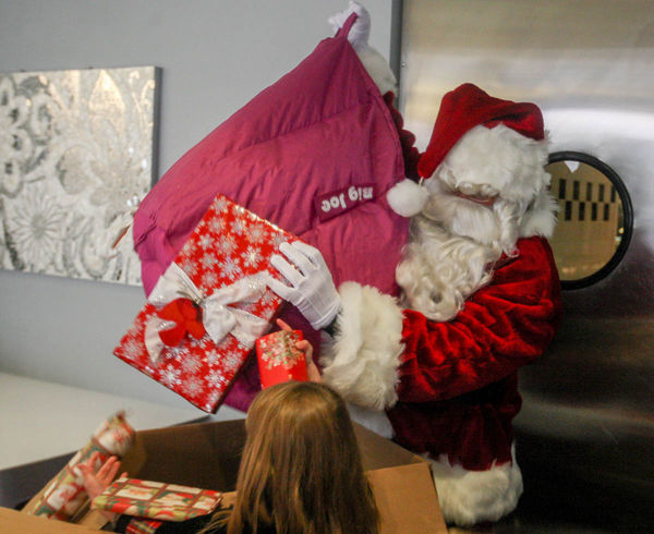 Santa pulls gifts from one of the boxes to present to the Kramer children.